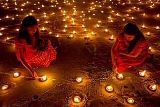 Image showing young girls lighting candles and clay lamps during Diwali night.